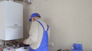 Mature man wearing blue overalls examines breaking of pipes from boiler