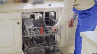 Mature master repairs dishwasher at the kitchen