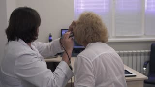 Medical professional tests the ear of an adult woman