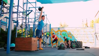 Men perform a crossfit exercise at the street