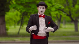 Mime is juggling with invisible balls in the park