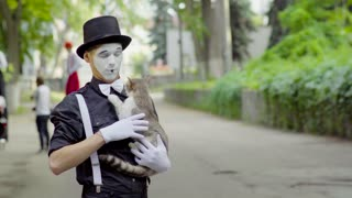 Mime joking with cat on the street