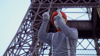 Mime looking at Eiffel tower through telescope