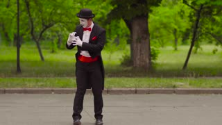 Mime trains invisible dog in the park