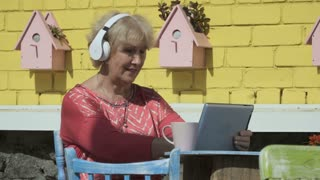 Modern old woman listen music in headphones and uses tablet