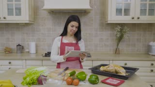 Modern woman looks the recipe of dinner at the tablet