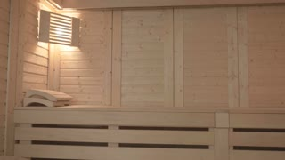 Modern wooden sauna with two benches and two lights