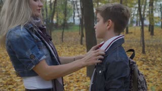 Mother and son embrace each other in the forest