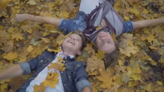 Mother and son lays on the ground and throws autumn leaves