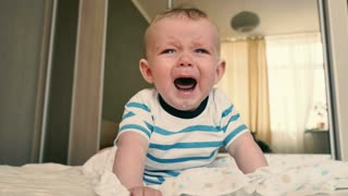 Mother comes to a crying baby to change his diaper
