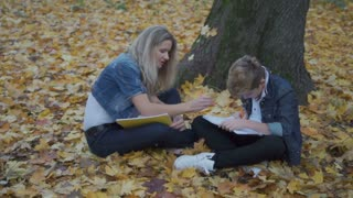 Mother help her son to do homework, family sit at autumn leaves