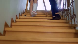 Mother help her son with broken leg to move down the stairs