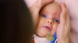 Mother touches a little daughter's head