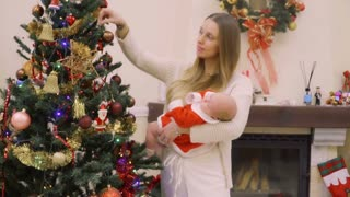 Mother with baby decorates Christmas tree