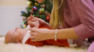 Mother with cute little daughter lays on floor at Christmas tree background