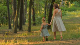 Mother with little girl walks in the park