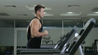 Muscular guy running on the treadmill