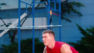 Muscular guy training with barbell at the sports ground