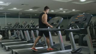 Muscular guy walks on treadmill in the gym