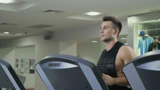 Muscular man runs in the running track