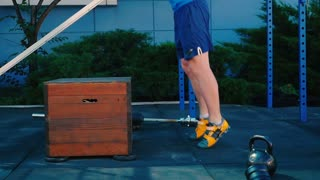 Muscular man training the legs and jump on the wooden box