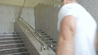 Muscular man with sportive bag moves up stairs