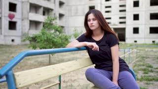 Nervous brunette girl is sitting near high building