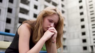 Nervous girl is sitting near high building