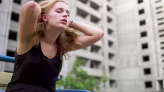 Nervous young girl is sitting near high building