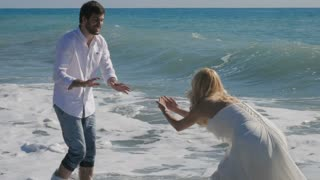 Newlyweds play and have fun in the ocean