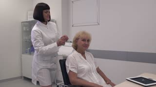 Nurse dressed an adult woman with a hearing aid