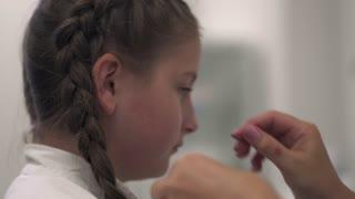 Nurse examines the ear of a girl