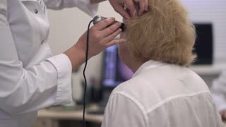 Nurse examines the ear of an adult woman.