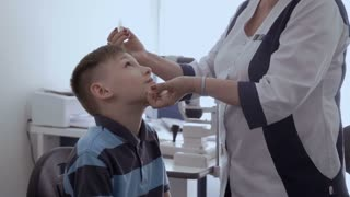 Oculist drip drops into the eyes of little patient
