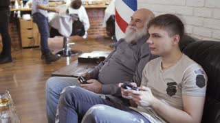 Old and young men waits their turn in barbershop and plays videogame