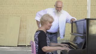 Old bearded man dancing during the wife playing piano