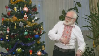 Old cheerful man dances near the christmas tree