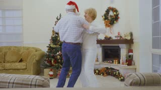 Old couple are dancing at home near christmas tree