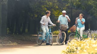 Old couple has a rest and drinks water when riding on bicycles in park