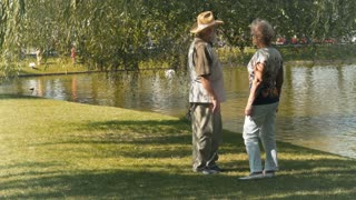 Old couple meets friends near the lake in park