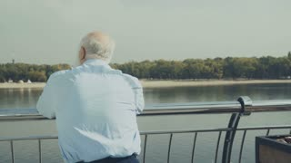Old gray-haired man looks at the beach near the river