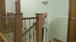 Old gray-haired man up the stairs at home