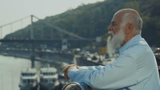 Old gray-haired man with beard relax near the river enjoying the view