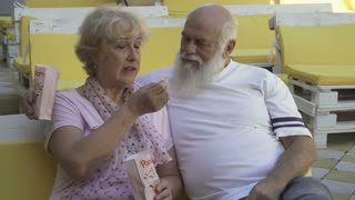 Old in love couple feeds each other the popcorn in summer cinema