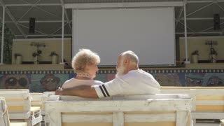 Old in love couple sits in summer cinema