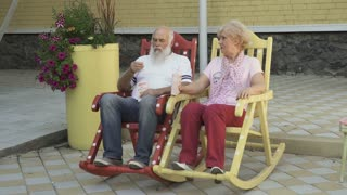 Old man and old woman rest in rocking chair and eats a popcorn
