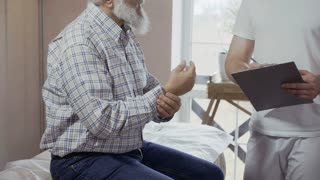 Old man complain to doctor about pain in elbow and wrist