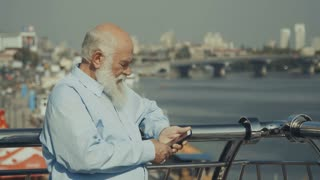Old man near the river with phone
