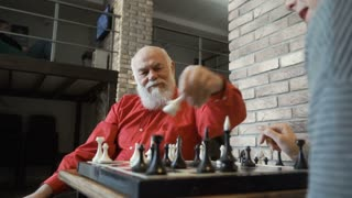 Old man play chess with granddaughter