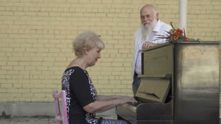 Old man presents a gift to wife playing on piano